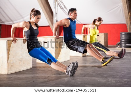 Group of young people working out their arms using boxes in a cross-training gym - stock photo