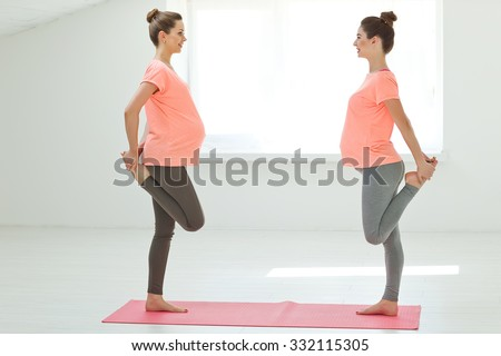 Group of young pregnant women doing relaxation exercise on exercising mat. series  - stock photo
