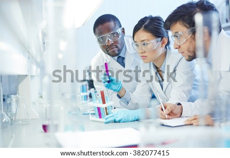 Group of young scientists studying new substances in flasks - stock photo