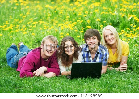 Group of young smiling happy students with laptop at spring green grass outdoors - stock photo