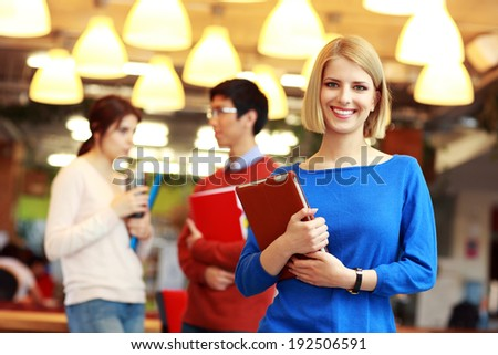 Group of young smiling students at university campus - stock photo