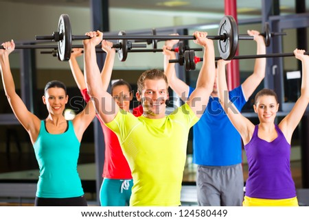 group of young sport people training with barbell at a gym for better fitness - stock photo