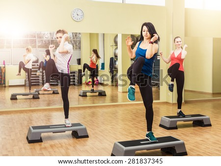 Group of young sportive women making step aerobics in the fitness class - stock photo