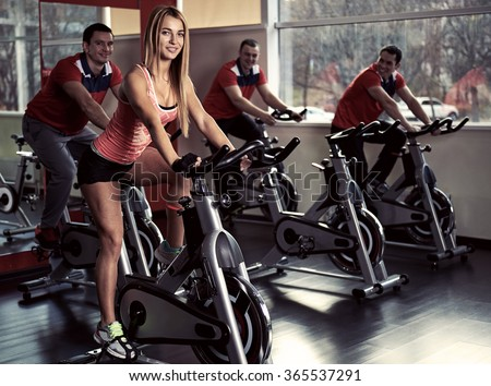 Group of young sporty people at class. Fitness team doing bicycle exercise in the gym. Sport, lifestyle and healthcare concept.