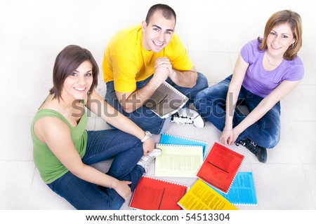 group of young students sitting on the floor with notebooks - stock photo