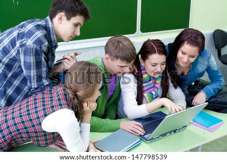 group of young students studying in the classroom with a laptop - stock photo