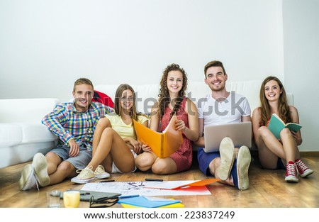 Group of young students studying together and preparing for exams in home interior - stock photo