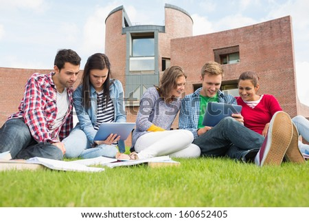 Group of young students using tablet PCs in the lawn against college building - stock photo