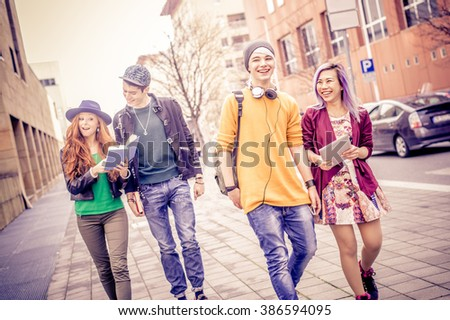Group of young students walking outdoors in a college campus - Young people portrait, concepts about youth, modern technologies, lifestyle and teens - stock photo