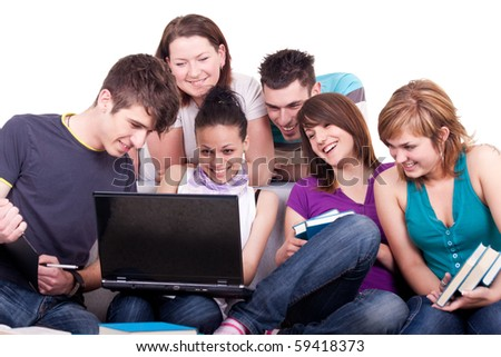 group of young teenagers looking at laptop and laughing