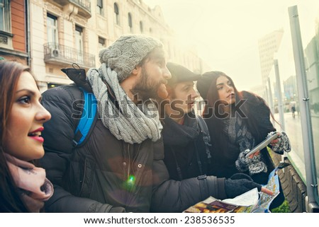 Group Of Young Tourists In The City Browsing Map Using Digital Tablet - stock photo