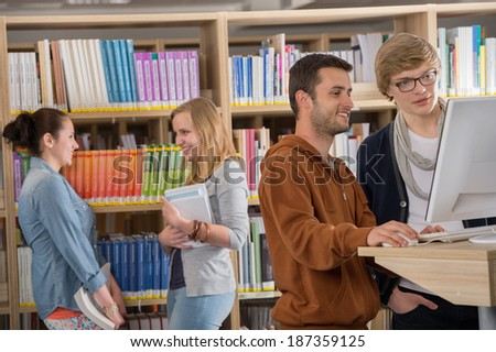 Group of young university students discussing in library - stock photo