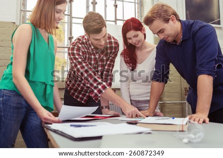 Group of Young White Friends Discussing the Project Paper at the Table While in Standing Position. - stock photo