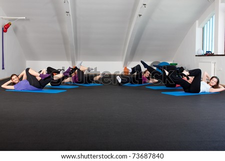 Group of young women doing aerobic exercises on the floor in a fitness club - stock photo