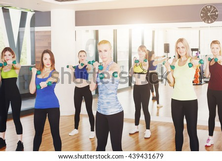 Group of young women in fitness class. Group of people making exercises. Girls with dumbbels. Healthy lifestyle, training, sport, gym studio. Attractive slim sporty girls in fitness club, aerobics. - stock photo