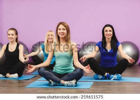 Group of young women in the gym centre. Yoga. Attractive young people meditate. fitness, sport, training, gym and lifestyle concept - group of smiling women with trainer meditating in yoga pose - stock photo