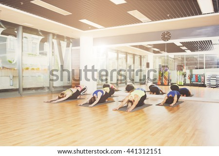 Group of young women in yoga class. Girls do stretching exercise, head to knee. Healthy lifestyle in fitness club - stock photo