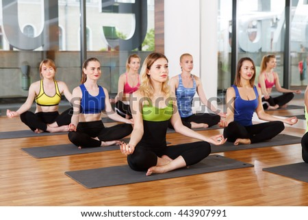 Group of young women in yoga class making exercises. Girls do meditation pose for relaxation. Healthy lifestyle in fitness club - stock photo