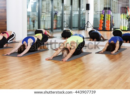 Group of young women in yoga class making exercises. Girls do stretching head to knee. Healthy lifestyle in fitness club - stock photo