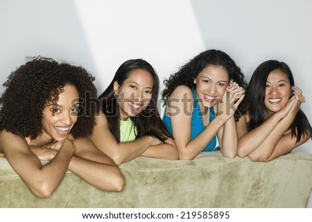 Group of young women lying on a bed looking at camera smiling - stock photo