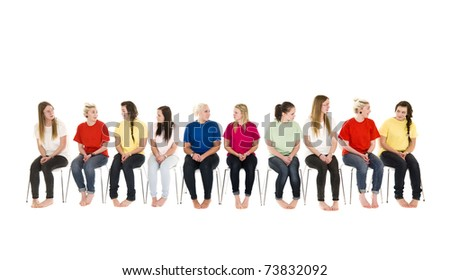 Group of Young women sitting on chairs wearing colorfull t-shirts - stock photo