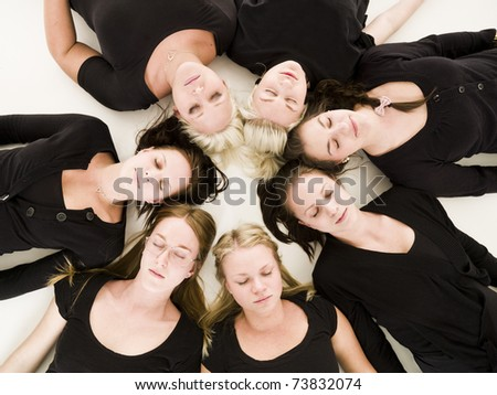 Group of Young Women with closed eyes lieing in a circle on white background