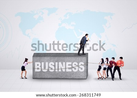Group of young workers move a business obstacle shaped a stone - stock photo