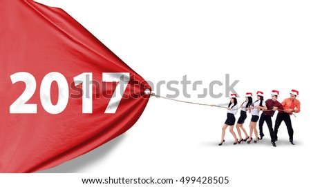 Group of young workers wearing christmas hat and pulling a big banner with number 2017, isolated on white background