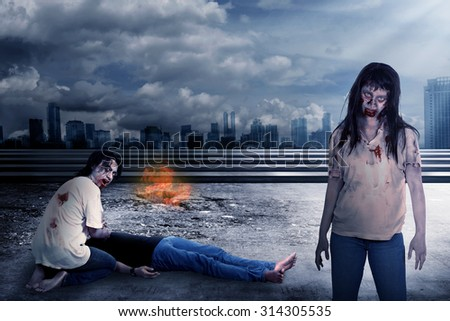 Group of zombie eating flesh with destroyed city background - stock photo