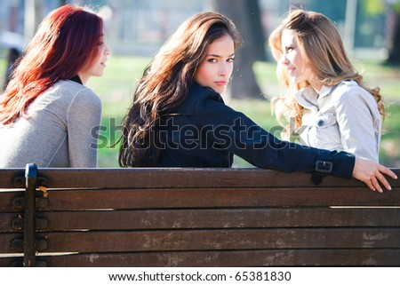 group og girlfriends talking in the park, autumn sunny day - stock photo