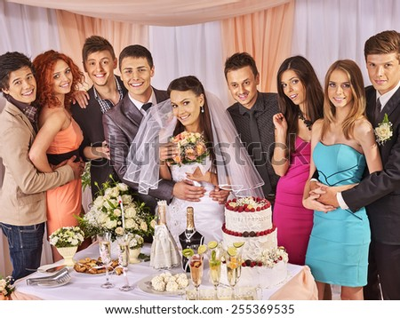 Group people at wedding table with cake. Bride in a veil - stock photo