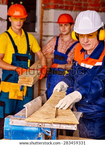 Group people  male builder with circular saw. - stock photo