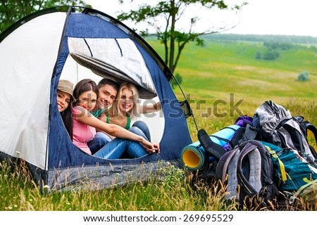 Group people with backpack in tent  hide from rain summer outdoor.