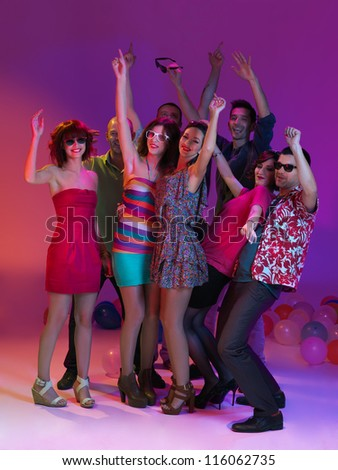 group photo of young men and women, holding each other, dancing and smiling, with their hans up - stock photo