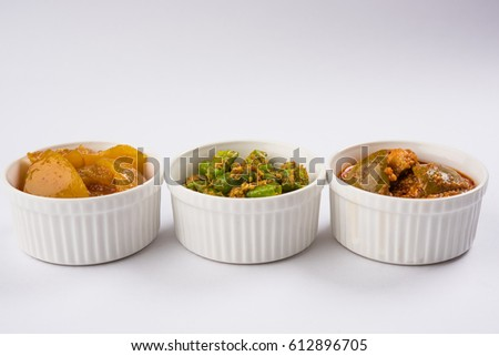 Group photograph of indian pickles like mango pickle , lemon pickle and green chilli pickle, sarved in white ceramic bowl, selective focus
