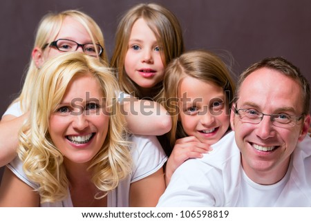 Group picture of a young family, father, mother and three children in bedroom - stock photo