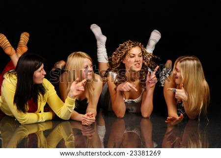 Group portrait. Four girls having dispute. Isolated on black background. - stock photo