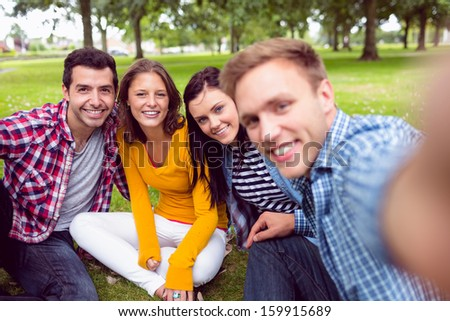 Group portrait of cheerful young college students in the park