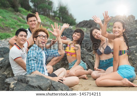 Group portrait of close friends having fun at coast line - stock photo