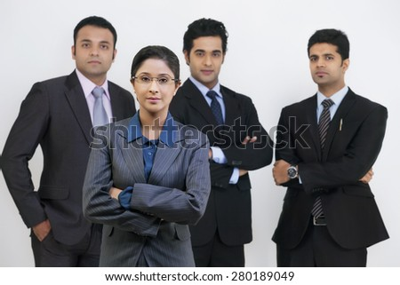 Group portrait of confident business people standing against gray background - stock photo