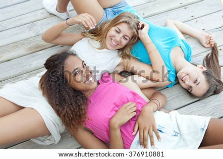 Group portrait of ethnically diverse adolescent girls friends laying together on a wooden deck, laughing smiling joyfully looking at camera, relaxing outdoors. Recreation travel lifestyle, teenagers. - stock photo