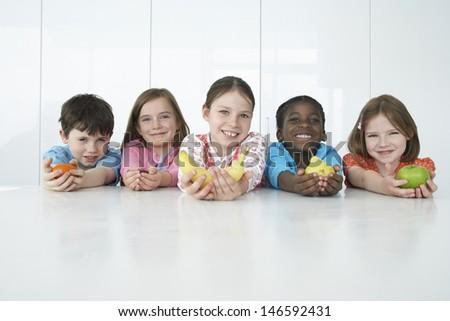 Group portrait of five multiethnic children holding various fruits - stock photo