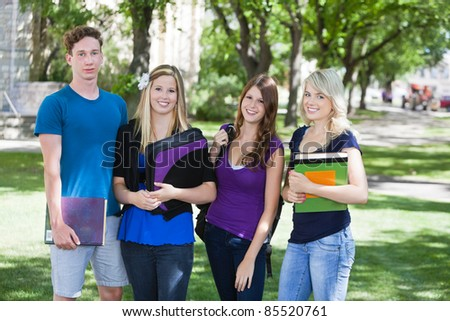 Group portrait of four college students on campus