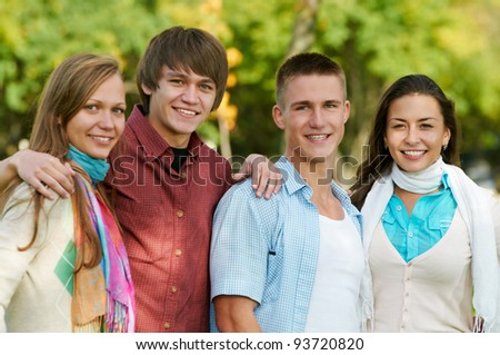 Group portrait of four smiling cheerful students outdoors in autumn - stock photo