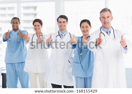 Group portrait of happy confident doctors gesturing thumbs up at hospital - stock photo
