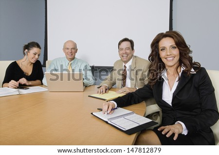 Group portrait of happy multiethnic businesspeople at conference table - stock photo