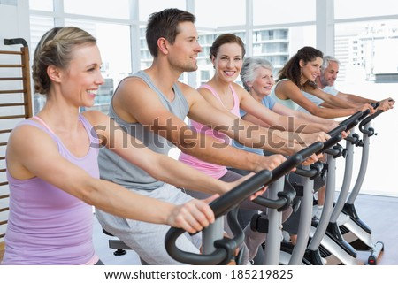 Group portrait of happy people working out at e exercise bike class in gym