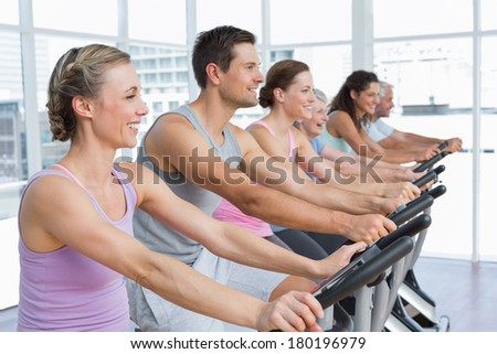 Group portrait of happy people working out at spinning class in gym - stock photo
