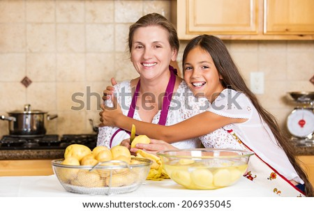 Group portrait of happy, smiling mother and daughter cooking dinner, preparing food isolated background home kitchen. Positive family emotions, face expression, life perception. Healthy eating concept - stock photo