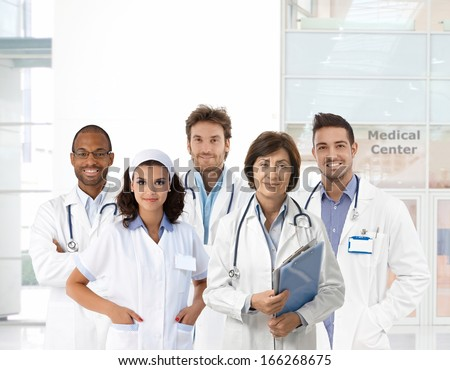 Group portrait of medical staff at clinic, looking at camera, smiling. - stock photo